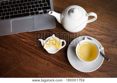 A cup of tea with lemon and pot with tea on the brown wooden table. Warm feeling and comfort concept