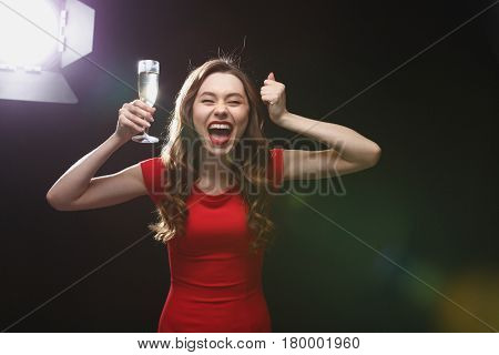 Happy excited young woman with glass of champagne standing and shouting over black background