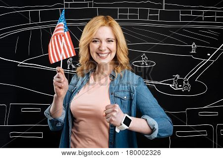 True sport fan. Positive delighted woman holding american flag and watching rugby while supporting her team