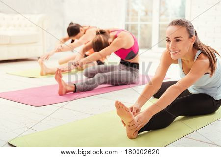 Limbering up. Pretty youthful lady is leaning forward and touching her foot while doing stretching at gym with friends.