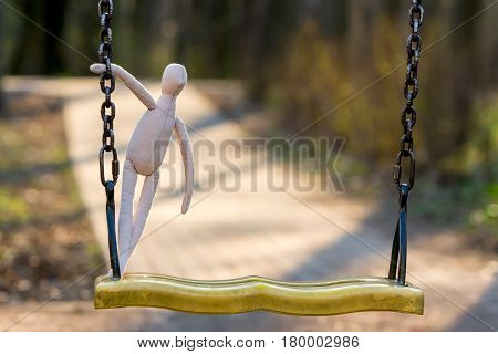 The sewn faceless doll stands on a swing and with one hand holds on to a chain in the background a path is laid out from a tile.
