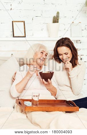 Enjoying conversations with you. Laughing emotional young woman sitting in the bedroom and taking care of aged grandmother while pensioner eating breakfast