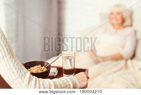 Supporting every patient. Skilled helpful proficient nurse standing in the hospital ward and taking care of elderly patient while holding breakfast tray