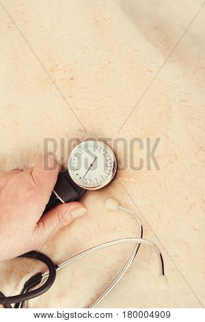 Useful device for my healthy lifestyle . Confident old aging woman sitting on the bed at home and measuring blood pressure while holding tonometer