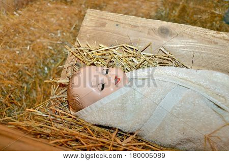 baby doll wrapped in towel on hay in manger