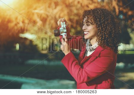 Laughing beautiful curly adult professional photographer woman in stylish trendy red coat photo shooting her friends with retro film camera outdoors with copy space for your advertising text message