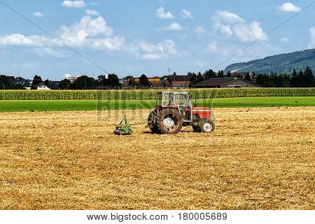 Tractor With Plough Doing Some Agricultural Seasonal Work At Field