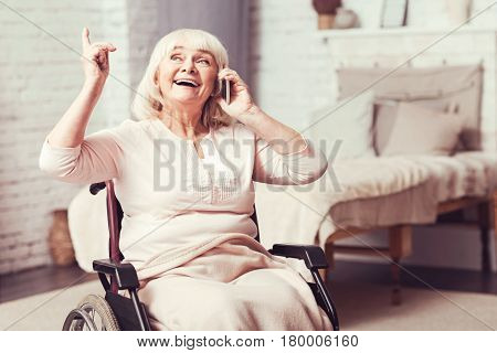 Full of positivity. Laughing old enable woman sitting in the wheelchair at home while smiling and using mobile