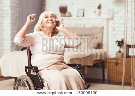 Sharing positive news. Optimistic senior enable woman sitting in the wheelchair at home while expressing positivity and using modern gadget