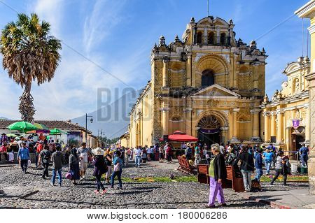 Antigua, Guatemala - April 2 2017: Pine needle procession carpets outside Hermano Pedro church during Lent against backdrop of Agua volcano in colonial town with most famous Holy Week celebrations in Latin America.