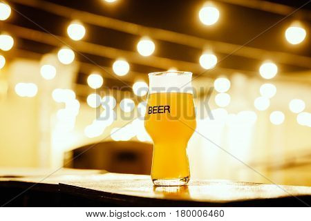 A glass of kraft beer on the background of lanterns, Flashlights