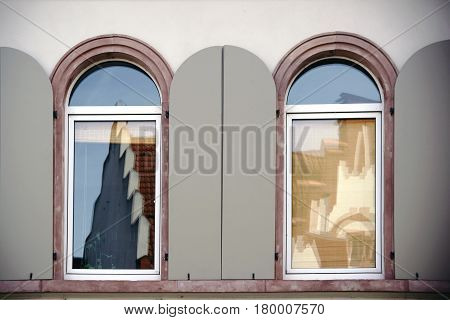 Two round-arch windows with open window shutters and reflections in the glass.