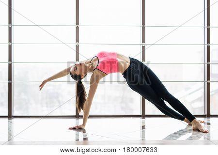 Woman Practicing Advanced Yoga Against A Window