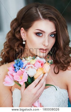 Beautiful young bride with wedding makeup and hairstyle indoor .Closeup portrait of young gorgeous bride in studio.Wedding