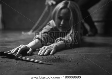 Not helpless anymore. Anxious stubborn young woman reaching a dagger lying near her making an tempt escaping