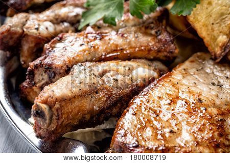 Juicy grilled meat pieces and herbs close up with selective focus.