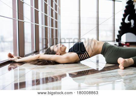 Young Woman Practice Yoga Matsyasana Against Windows In Studio.