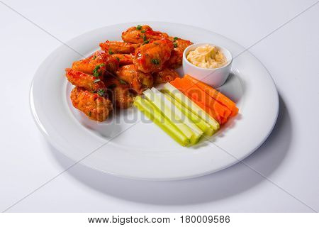 Spicy Bbq Buffalo Chicken Wings Sitting On Plate Garnished With Carrot And Celery Sticks With Blue C