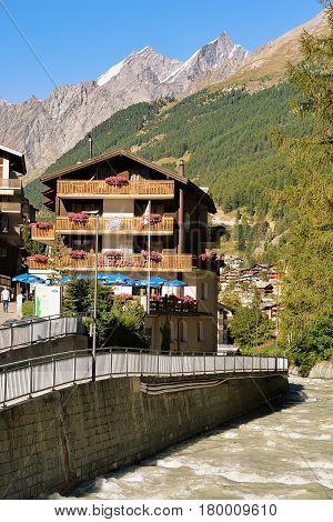 Traditional Swiss Chalets And Gornera River In Resort Town Zermatt