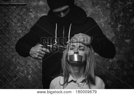 Hiding from law behind a mask. Barbaric cruel attacking villain feeling powerful and making his hostage feel hopeless by holding a gun against her head