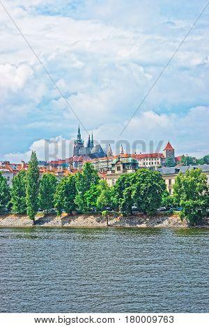 Vltava River embankment with Prague Old Town Czech Republic. Strakova Academy with St Vitus Church on the background
