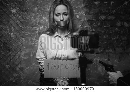 Price tag. Protectless scared young woman being kept in some dark place and posing for a video while her captor threatening her with a gun