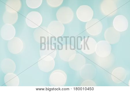 Pale aqua blue and white bokeh background of soft twinkling lights.