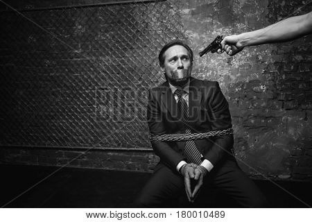 Do not shoot me. Miserable anxious oppressed man looking terrified while sitting helplessly tied to a chair and his abductor pointing a gun at him