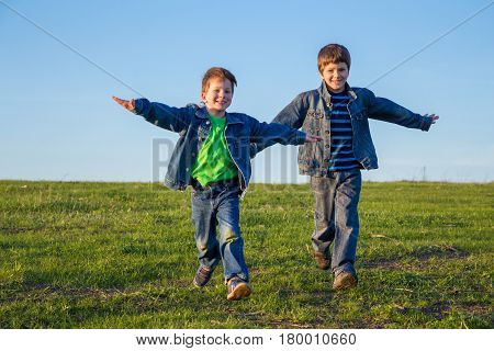 Two happy brothers running together on hill with hands as wings against blue sky