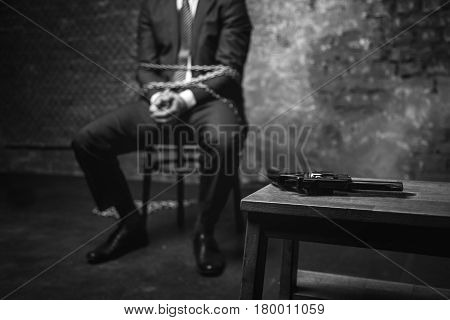 Perfect chance. Smart quick witted businessman coming up with a plan of escape while looking at the gun lying on the table nearby