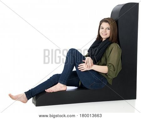 A beautiful teen girl sitting, relaxed on a curvy black structure.  On a white background.
