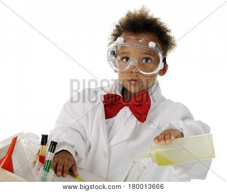 An adorable preschool chemist in safety goggles and lab coat mixing chemicals on his science table.  On a white background.