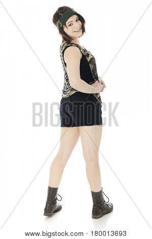A beautiful teen happily looking back at the viewer as she stands her her camouflage headband and sleeveless shirt.  She's also in combat boots and black shorts.  On a white background.