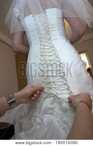 A friend of the bride bride corset laces on a wedding dress. Bride's corset in a white long wedding dress is laced with a thin white ribbon. Unbound ribbon on the bride's corset on the wedding day.