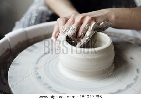 The woman's hands close up the masterful studio of ceramics works with clay on a potter's wheel