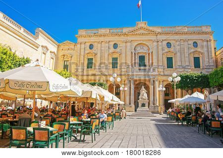 People Resting In Open Air Cafes At Republic Square Valletta