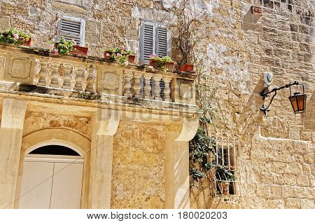 Street With Lantern And Balcony With Flowers In Mdina