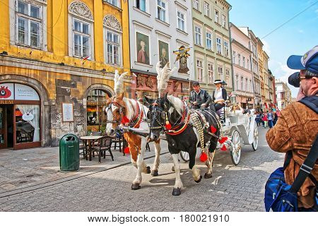 Krakow Poland - May 1 2014: Man taking photo of Horse fiacre passing by on the streets of the Old town of Krakow Poland