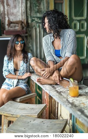 Two girls in the bar outdoors. One sits on the wooden rack with crossed legs, other sits on the stool. They wear bikini tops, light shirts with patterns, shorts, sunglasses. Women look on each other.