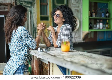 Joyful smiling girls in the bar outdoors. Women play arm wrestling on the wooden bar rack. They wear light shirts with patterns, shorts, sunglasses. Horizontal.