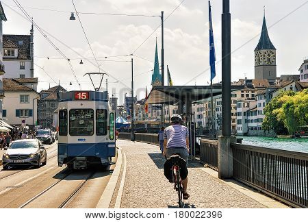Running Tram And Man Riding Bicycle At Limmatquai In Zurich