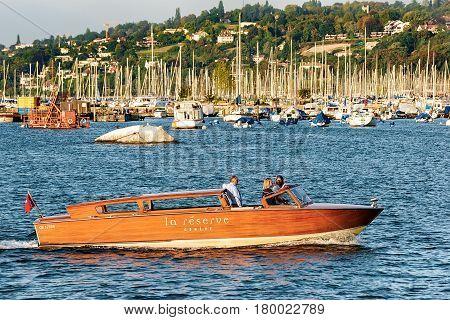 Geneva Switzerland - August 30 2016: Boat with people on Geneva Lake near Promenade du Lac in summer Geneva Switzerland.