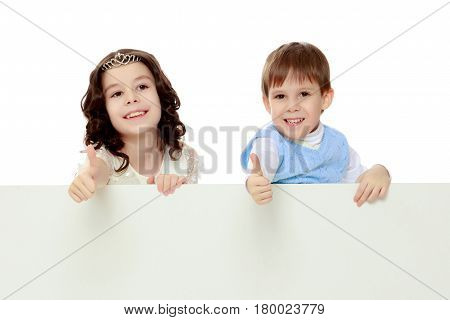 A boy and a girl peeping from behind the white banner.Children show a gesture all okay.Isolated on white background.
