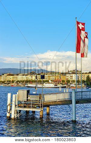 Pier with Swiss flags on Geneva Lake near Promenade du Lac in summer Geneva Switzerland.