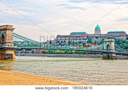 Buda Castle With Chain Bridge Over Danube River In Budapest
