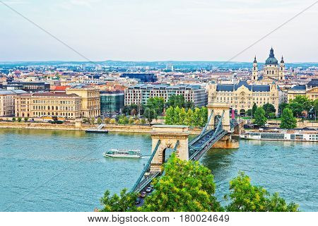 Chain Bridge above Danube Canal and St Stephen Basilica at Pest city center in Budapest Hungary