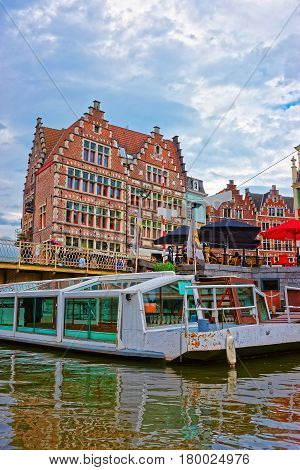 Ferry Boat And Cafes With People On Graslei In Ghent