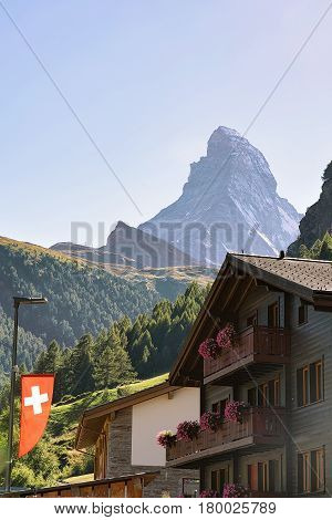 Traditional Chalet In Zermatt With Matterhorn Peak With Swiss Flag