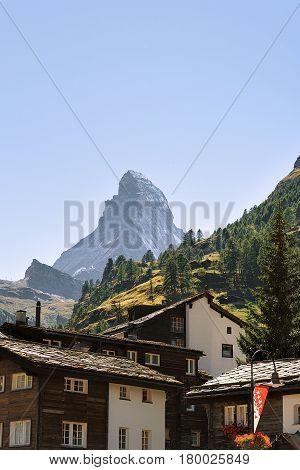 Traditional Swiss Chalets In Zermatt With Matterhorn Peak With Flag