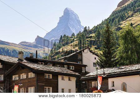 Traditional Swiss Chalets In Zermatt With Matterhorn Peak With Flags